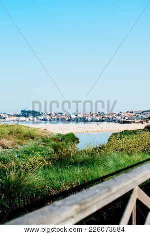 Beautiful view of the beach Praia America in town Nigran, Galicia, Northen Spain. Coastline landscape with white sand and houses on background in early morning