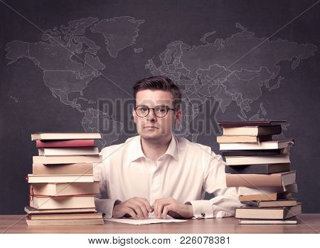 A young ambitious geography teacher in glasses sitting at classroom desk with pile of books in front of world map drawing on blackboard, back to school concept.