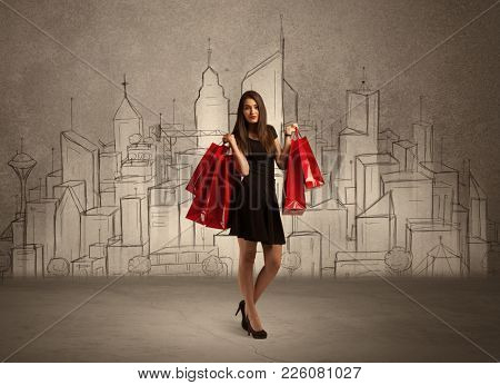 An attractive young lady standing with red shopping bags in front of drawn city landscape silhouette concept