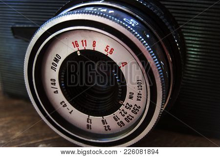 Old Photo Camera On Wooden Background. Vintage Retro Style Poster Of Film Camera, 1950s Rare Model.