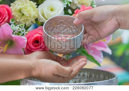Songkran Thai Festival Concept : Close-up Pour Water On Hands Of Revered Elders, Gives Blessing In S