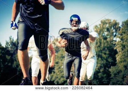 American Football Players Running Towards The Goal Line