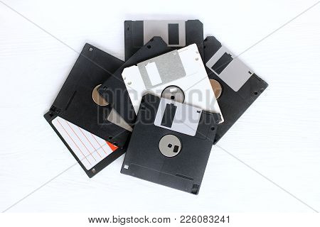 One White Computer Disk Among A Variety Of Dusty And Old Black Media / Information Is Not Like Every