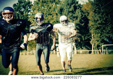 American Football Players Running Towards The Goal Line, Cheerleaders Rooting In The Background
