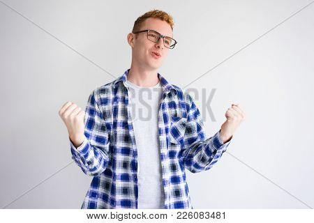 Excited Red Haired Caucasian Student Raising Fist In Success. Young It Developer Wearing Glasses Sho