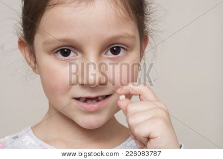 Little Girl And A Milk Tooth