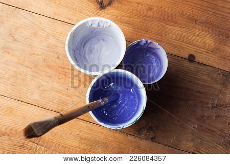 Purple Acrylic Paint In Different Colors, Top View, Paper Cups With Paint And Brush, Wooden Table