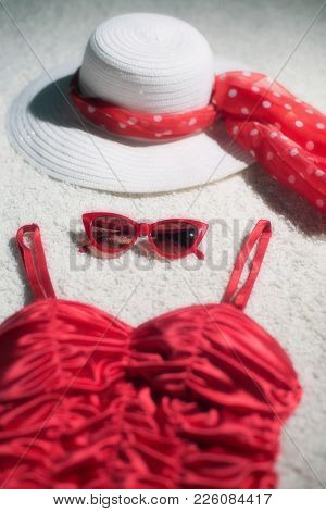 Vintage Summer Hat, Red Sunglasses And Swimsuit Displayed On White Carpet Floor.