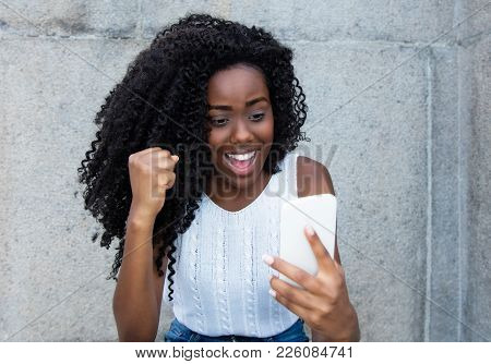 Africa American Woman Receiving Good News On Phone Outdoors