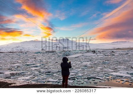 Woman In Silhouette Photographing The Glacier Lagoon In Iceland At Sunset
