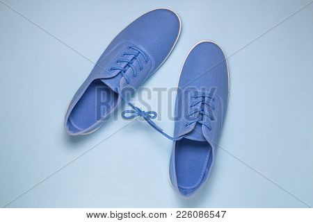 Flat Lay Of Blue Sneakers Tied With Shoelaces On Blue Pastel Blue Background. Minimal Concept