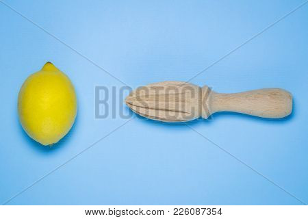 Flat Lay Of Lemon And Wooden Juicer On Pastel Blue Background Minimal Concept