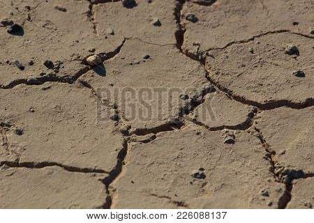 Part Of A Huge Area Of Dried Land Suffering From Drought - In Cracks.