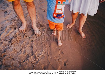 Theme Is A Family Beach Holiday. Legs Barefoot Three People Mum, Dad And Son On A Sandy Beach Near T