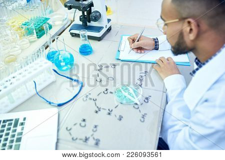 High Angle Portrait Of Young Middle-eastern Scientist Studying Chemical Structures In Modern Medical
