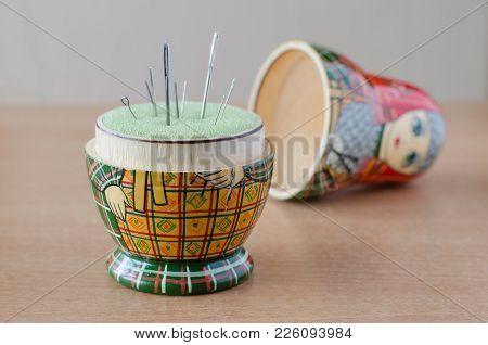 Matryoshka Doll Pincushion. Sewing Needle. Close Up. Blurred Background.