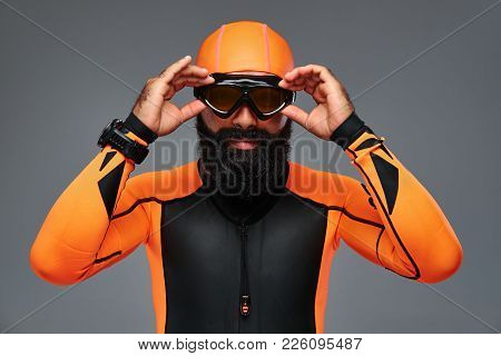 Close-up Portrait Of A Bearded Male In Orange Neoprene Diving Suit And Dive Mask Isolated On Grey Ba