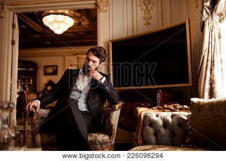 Thoghtful Prosperous Male Involved In Business, Dressed In Formal Suit, Sits In Royal Room On Comfor