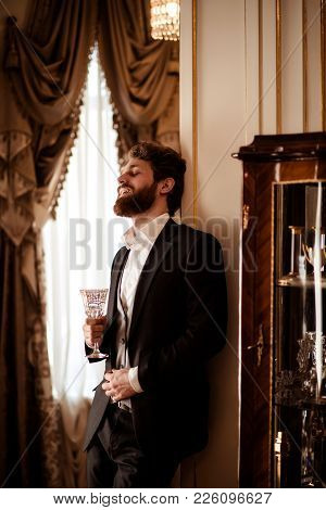 Vertical Shot Of Pleased Bearded Young Businessman Wears Black Formal Suit Holds Glass And Drinks Be