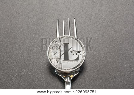Silver Litecoin Physical Coin On A Fork Illustrating A Cryptocurrency Split Concept.