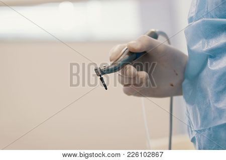 Dentist's Bloody Hands With Drill In Dental Office