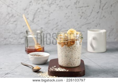 Healthy Diet Breakfast. Overnight Oatmeal With Chia Seeds, Bananas, Peanut Butter, Honey In A Glass