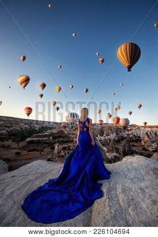 Back View Of Blonde Female Dressed In Elegant Long Blue Dress, Stands Back On High Hill, Admires Man