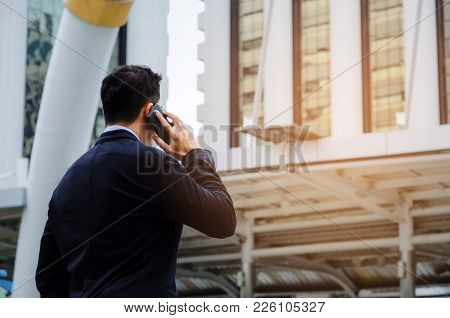 Back View Of Young Smart Business Man Wearing Black Suit Making Phone Call With Mobile Smart Phone I