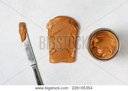Toast With Peanut Butter,  Jar Of Peanut Butter,  Knife On A Light Gray Background. View From Above