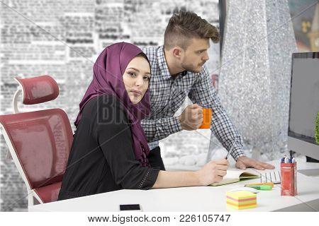 International Multicultural Team At Work: Asian Muslim Woman And Caucasian Man