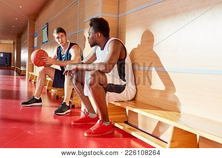 Unsmiling Handsome Young Multiethnic Basketball Friends Sitting On Bench And Discussing Match After
