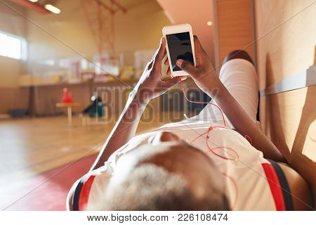 Tired African Basketball Player Waiting For Training And Relaxing On Bench Enjoying Music In Earphon