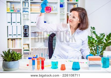 Female Scientist Holding Laboratory Flask In Hand. Researcher Researching In The Laboratory. Reagent