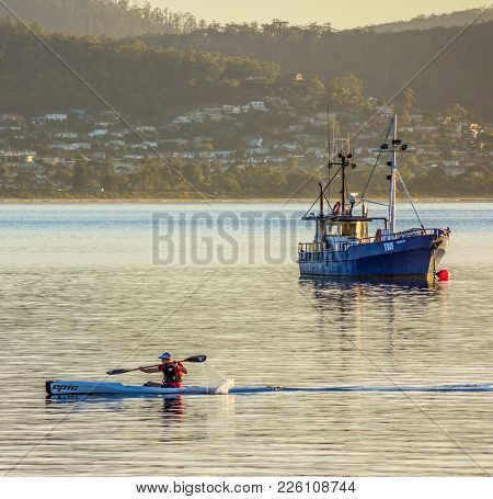 Hobart, Tasmania, Australia - 28 February 2014: Sea Kayaker Paddling Past Fishing Boat In The Early