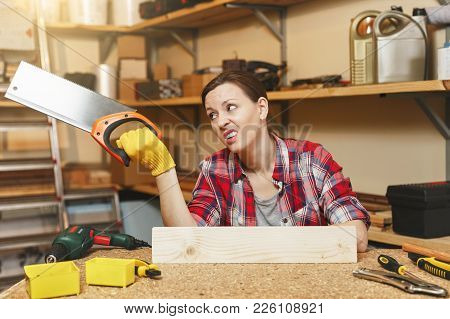 Beautiful Tired Caucasian Young Brown-hair Woman In Plaid Shirt, Gray T-shirt, Yellow Gloves Sawing