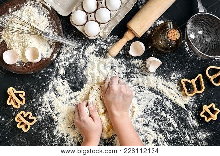 Woman's Hands Knead Dough On Table With Flour, Eggs And Ingredients. Top View.