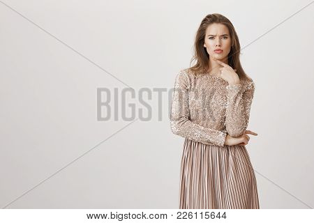Portrait Of Upset Beautiful European Female In Trendy Evening Dress Frowning And Holding Index Finge