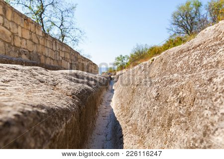 Road In The Rock And Deep Gauge From The Medieval Transport In Medieval Cave City-fortress Chufut-ka