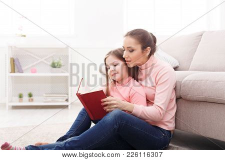 Little Girl And Her Mom Reading Book Sitting On The Floor At Home. Mothers Day, Relationship, Mother
