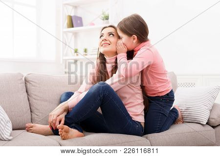 Mother With Her Daughter Sitting On The Sofa. The Girl Telling A Secret. Mothers Day, Relationship,