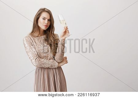 Portrait Of Sexy Fashionable Woman In Glittering Evening Dress, Holding Champagne, Frowning And Bein