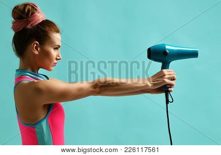Happy Young Brunette Woman Pointing Hair Dryer On Blue Mint Background. Hair Style Beauty Concept