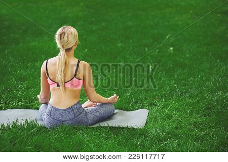 Young Woman Outdoors, Meditation Exercises, Back View. Girl Does Lotus Pose For Relaxation. Wellness