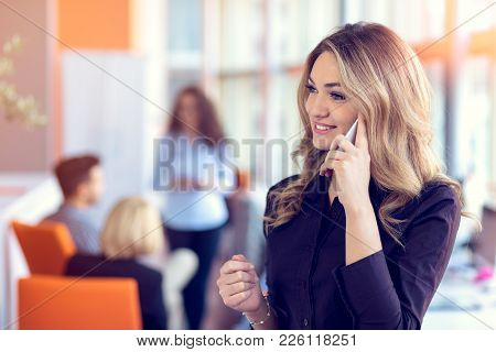 Young Attractive Businesswoman Talking On Mobile Phone In Office, Her Colleagues On The Background.