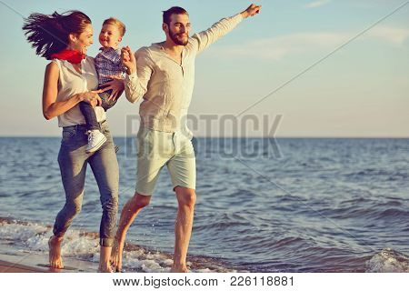 Portrait Of Happy Family And Baby Enjoying Sunset In The Summer Leisure.