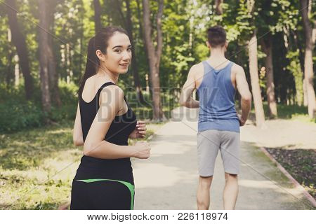 Young Happy Sporty Couple Jogging In Green Park During Morning Workout, Selective Focus
