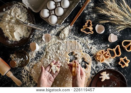 Close-up Of A Woman's Hand With A Dough. The Woman Is Cutting A Cookie With A Cookie Cutter In The S