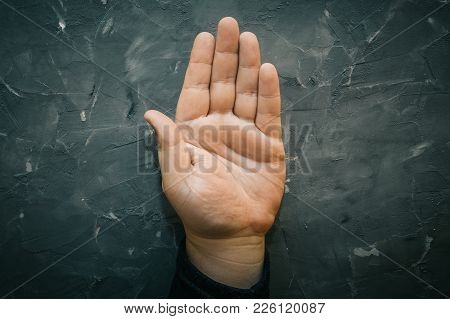 Palmistry Concept. Male Hand On Gray Table With Open Palm, Top View, Chiromancy Lines Of Fortune