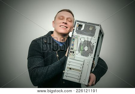 Happy Computer Tecnician Man Hugs A Computer Isolated On Dark Background. Gamer Man Love His Compute