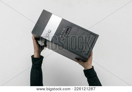 Male Hands Is Holding A Computer Above A Head Isolated On Gray Background. First Computer Help.